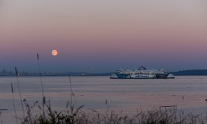 Moonrise over Vancouver with ferry in foreground, seen from Seymour Shores